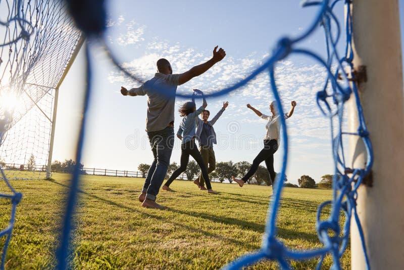 Τέσσερις νέοι ενήλικοι ενθαρρυντικοί ένας σημειωμένος στόχος στο ποδοσφαιρικό παιχνίδι στοκ φωτογραφία