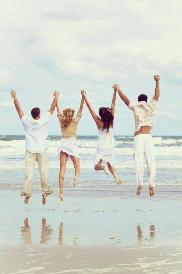 Τέσσερις νέοι δύο ζεύγη που πηδούν στον εορτασμό στην παραλία στοκ εικόνες