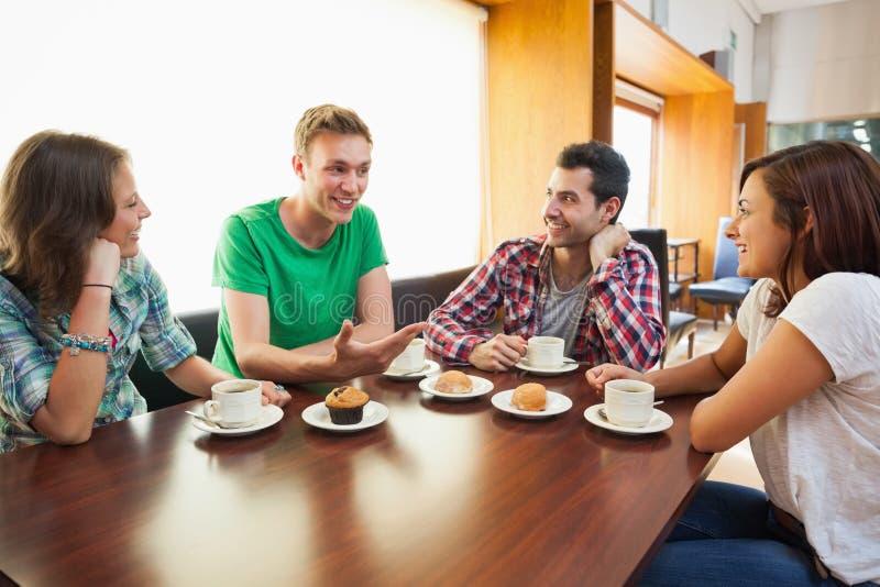 Τέσσερις περιστασιακοί σπουδαστές που έχουν να κουβεντιάσει φλιτζανιών του καφέ στοκ φωτογραφίες