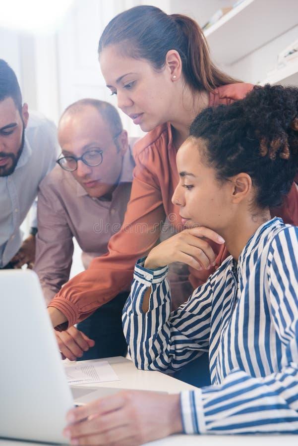 Τέσσερις συνάδελφοι εργασίας συλλέγουν γύρω από έναν υπολογιστή στοκ εικόνες