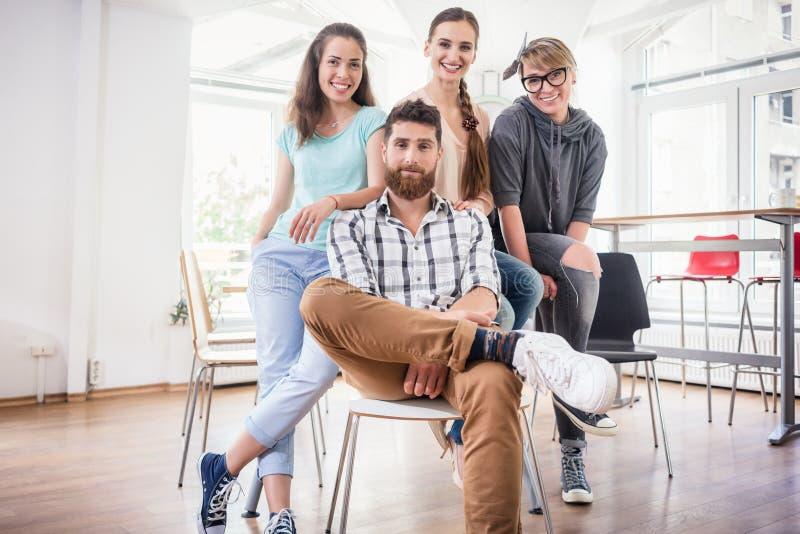 Τέσσερις συνάδελφοι που φορούν τα περιστασιακά ενδύματα κατά τη διάρκεια της εργασίας σε ένα σύγχρονο χ στοκ φωτογραφία