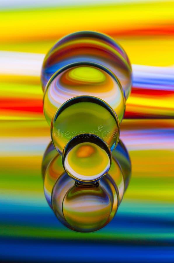 Τέσσερις σφαίρες κρυστάλλου γυαλιού σε μια σειρά με ένα ουράνιο τόξο της ζωηρόχρωμης ελαφριάς ζωγραφικής πίσω από τους στοκ εικόνες