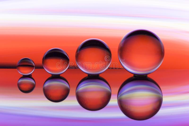 Τέσσερις σφαίρες κρυστάλλου σε μια σειρά με τις ζωηρόχρωμες ραβδώσεις του ουράνιου τόξου χρωματίζουν πίσω από τους στοκ φωτογραφίες με δικαίωμα ελεύθερης χρήσης