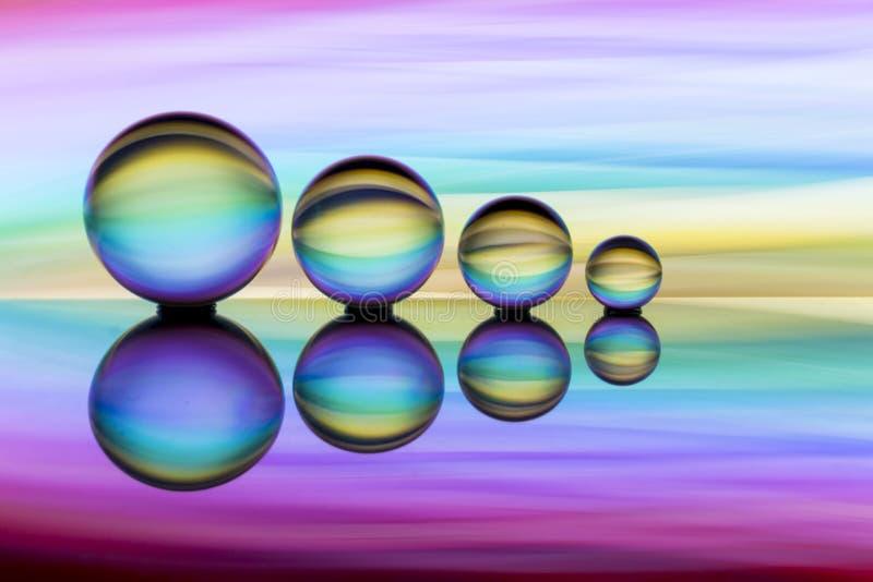 Τέσσερις σφαίρες κρυστάλλου σε μια σειρά με τις ζωηρόχρωμες ραβδώσεις του ουράνιου τόξου χρωματίζουν πίσω από τους στοκ φωτογραφία με δικαίωμα ελεύθερης χρήσης