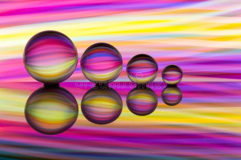 Τέσσερις σφαίρες κρυστάλλου σε μια σειρά με τις ζωηρόχρωμες ραβδώσεις του ουράνιου τόξου χρωματίζουν πίσω από τους στοκ φωτογραφία