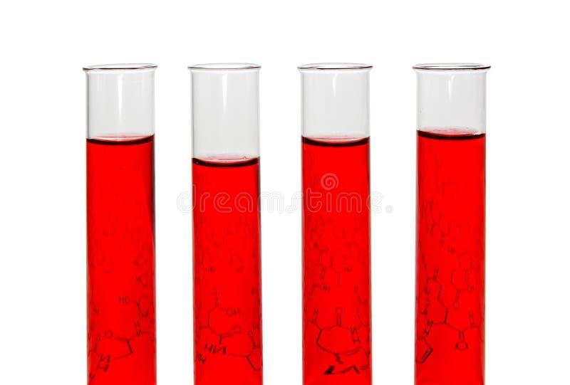 Τέσσερις σωλήνες δοκιμής με τα κόκκινα υγρά και το φύλλο του εγγράφου με τον τύπο στοκ φωτογραφίες