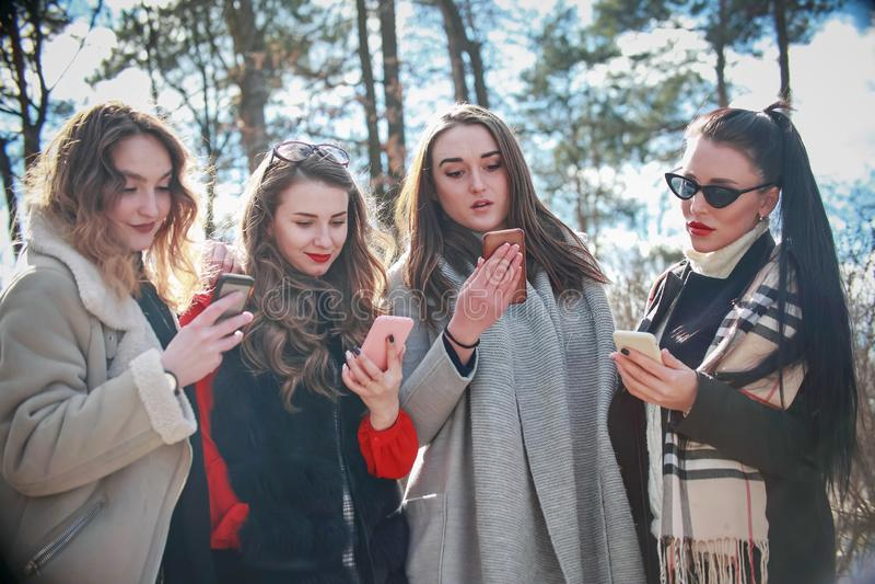 Τέσσερις φίλες γράφουν στο τηλεφωνικό περπάτημα στοκ φωτογραφίες