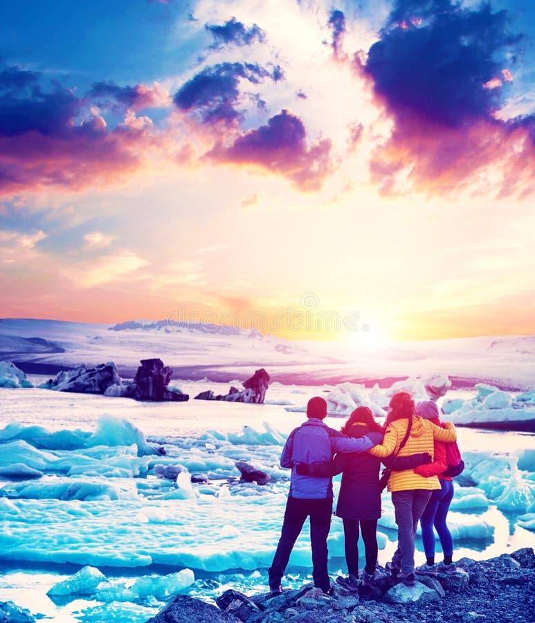 Τέσσερις φίλοι εξετάζουν το ηλιοβασίλεμα στη διάσημη λιμνοθάλασσα πάγου Jokulsarlon στην Ισλανδία Εξωτικές χώρες Καταπληκτικές θέ στοκ εικόνα