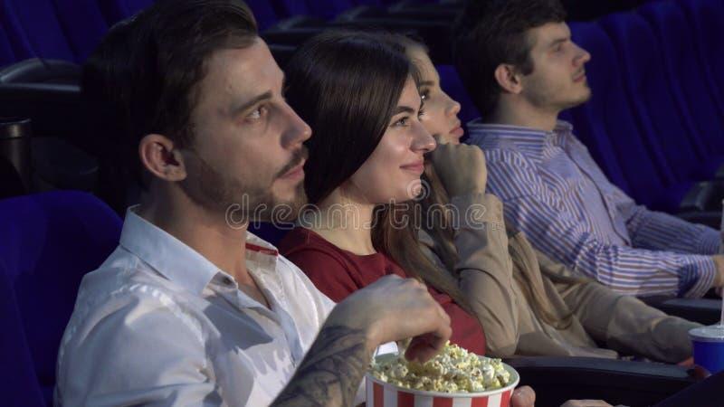 Τέσσερις φίλοι κάθονται στην αίθουσα κινηματογράφων και προσέχουν τον κινηματογράφο στοκ φωτογραφίες