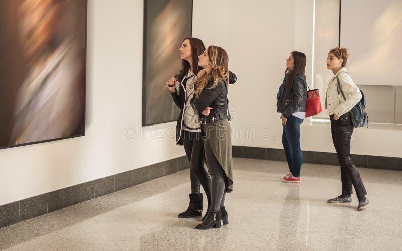 Τέσσερις φίλοι κοριτσιών που εξετάζουν τη σύγχρονη ζωγραφική στο γκαλερί τέχνης στοκ φωτογραφία με δικαίωμα ελεύθερης χρήσης