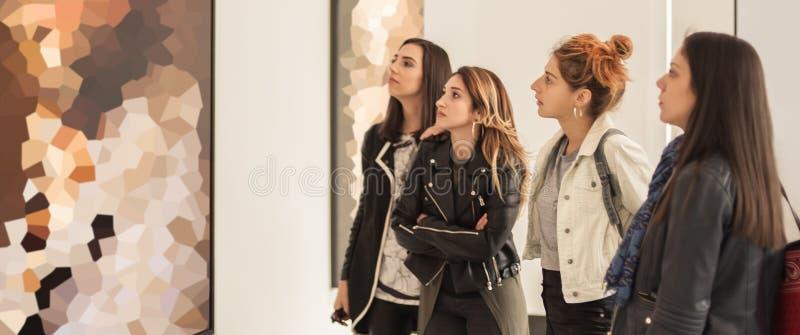 Τέσσερις φίλοι κοριτσιών που εξετάζουν τη σύγχρονη ζωγραφική στο γκαλερί τέχνης στοκ φωτογραφία