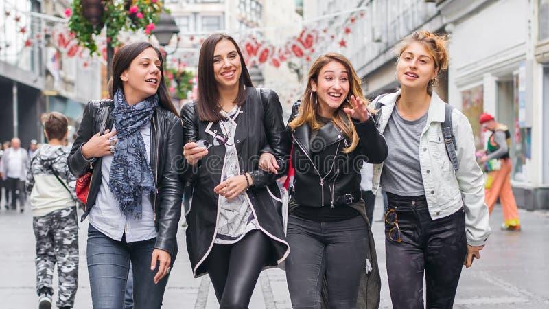 Τέσσερις φίλοι, κουτσομπολιό και κατοχή κοριτσιών της διασκέδασης στην οδό στοκ εικόνες