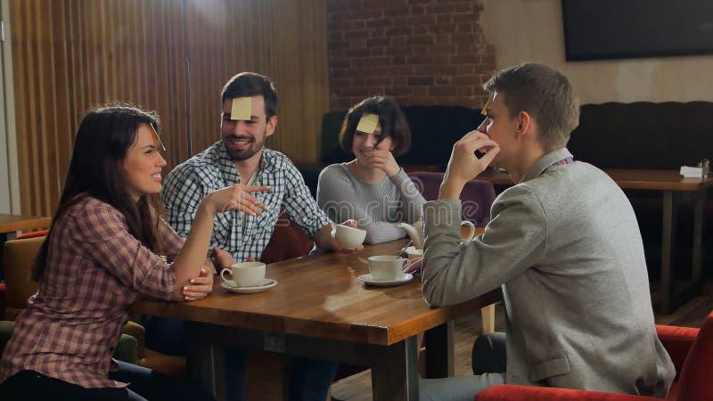 Τέσσερις φίλοι παίζουν μαζί ποιοι είμαι στον καφέ στοκ εικόνες