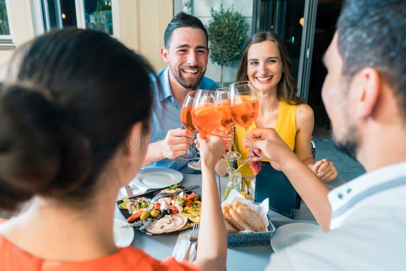 Τέσσερις φίλοι που ψήνουν μαζί με ένα κρύο που αναζωογονεί το οινοπνευματώδες ποτό στοκ εικόνα με δικαίωμα ελεύθερης χρήσης
