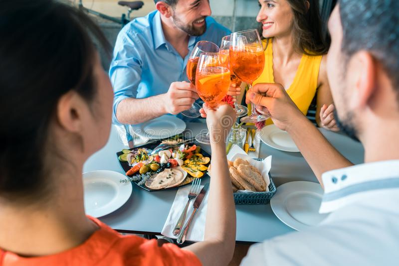 Τέσσερις φίλοι που ψήνουν μαζί με ένα κρύο που αναζωογονεί το οινοπνευματώδες ποτό στοκ εικόνες με δικαίωμα ελεύθερης χρήσης