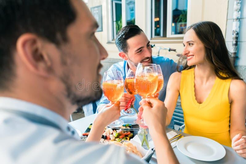 Τέσσερις φίλοι που ψήνουν μαζί με ένα κρύο που αναζωογονεί το οινοπνευματώδες ποτό στοκ φωτογραφία