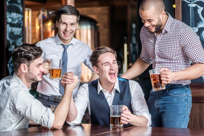 Τέσσερις φίλοι αγωνίζονται σε ετοιμότητα τους πίνουν την μπύρα και ξοδεύουν το χρόνο τ στοκ εικόνα