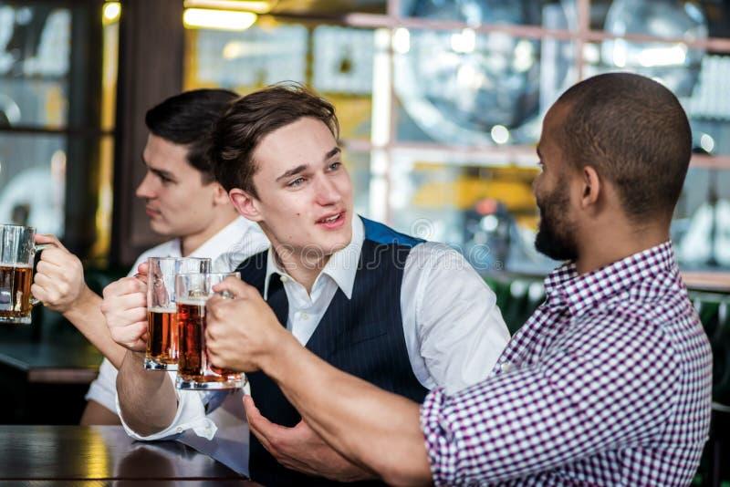 Τέσσερις φίλοι επιχειρηματιών πίνουν την μπύρα και ξοδεύουν το χρόνο μαζί στο α στοκ φωτογραφία με δικαίωμα ελεύθερης χρήσης