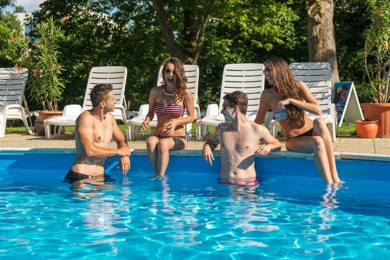 Τέσσερις φίλοι που έχουν τη διασκέδαση στην πισίνα στοκ εικόνα με δικαίωμα ελεύθερης χρήσης