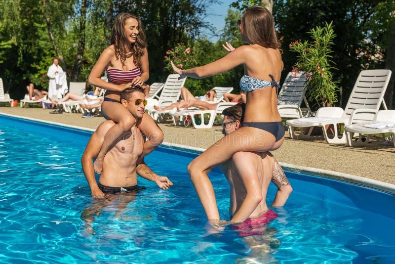 Τέσσερις φίλοι που έχουν τη διασκέδαση στην πισίνα στοκ εικόνες