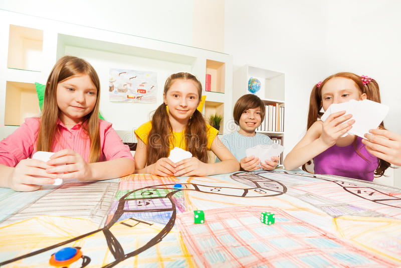 Τέσσερις φίλοι που παίζουν το παιχνίδι καρτών στον πίνακα τυχερού παιχνιδιού στοκ φωτογραφία με δικαίωμα ελεύθερης χρήσης