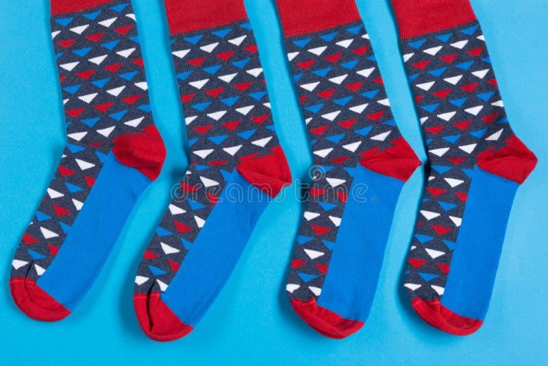 Τέσσερις χρωματισμένες κάλτσες βρίσκονται σε ένα μπλε υπόβαθρο, δύο ζευγάρια, έννοια στοκ εικόνες με δικαίωμα ελεύθερης χρήσης