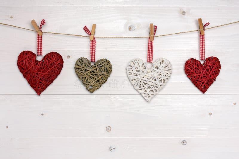 Τέσσερις ψάθινες καρδιές που κρεμούν στο σχοινί Ανασκόπηση ημέρας βαλεντίνων στοκ εικόνες