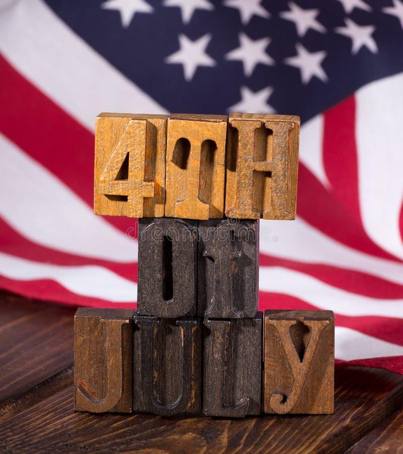 Τέταρτο του εμβλήματος Ιουλίου με το υπόβαθρο αμερικανικών σημαιών στοκ φωτογραφία