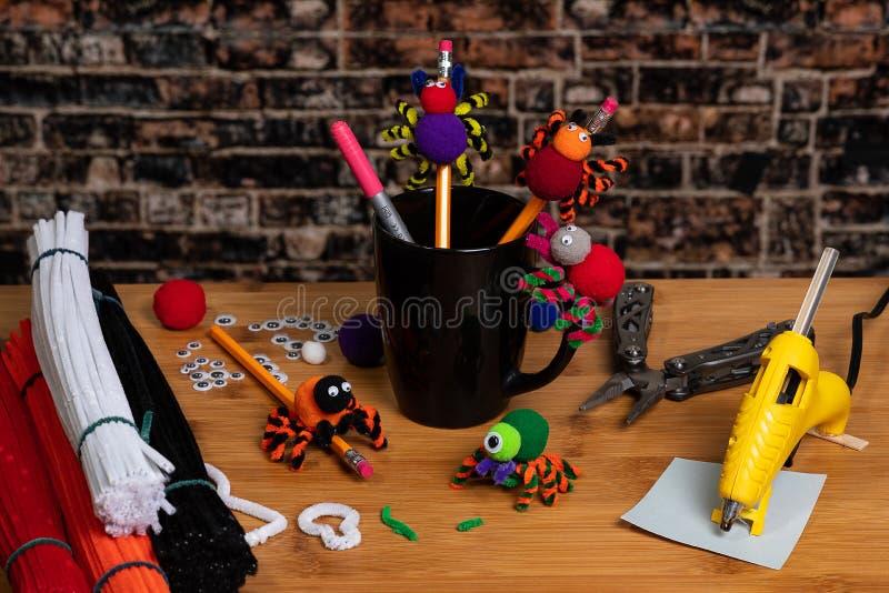 Τέχνες αποκριών διασκέδασης Αράχνες φιαγμένες από pom poms και καθαριστές σωλήνων Συνδεμένος με τα μολύβια Τέχνες οικογένειας και στοκ εικόνα