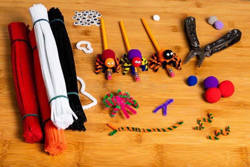 Τέχνες αποκριών διασκέδασης Αράχνες φιαγμένες από pom poms και καθαριστές σωλήνων Συνδεμένος με τα μολύβια Τέχνες οικογένειας και στοκ φωτογραφία