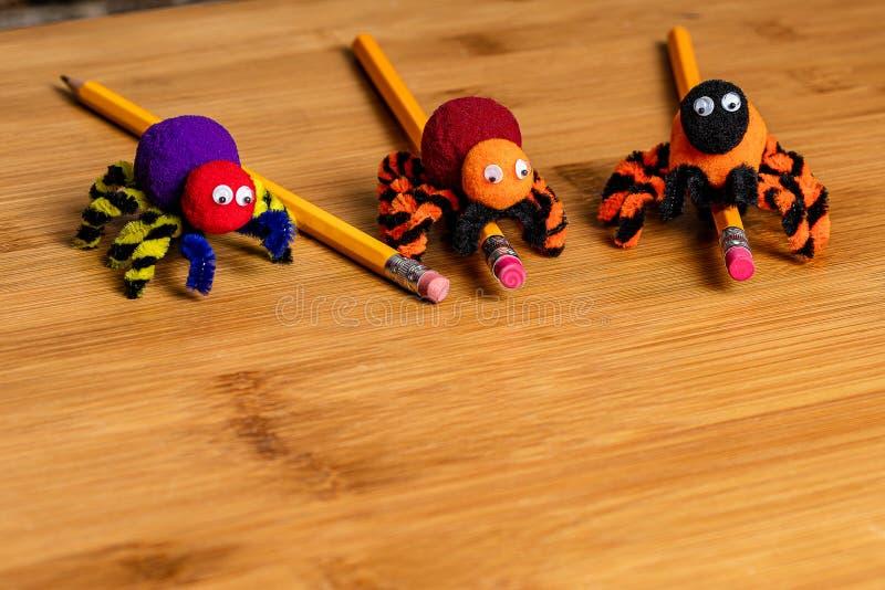 Τέχνες αποκριών διασκέδασης 3 αράχνες φιαγμένες από pom poms και καθαριστές σωλήνων Συνδεμένος με τα μολύβια Αρνητικό διάστημα γι στοκ φωτογραφία