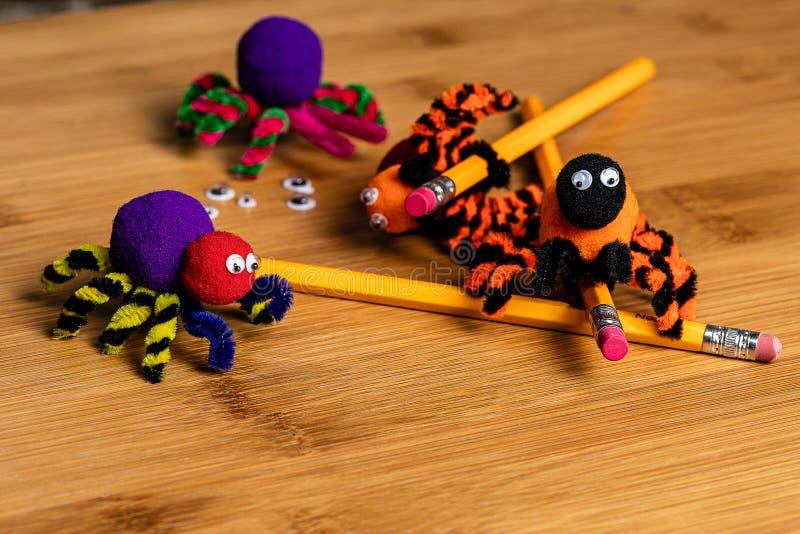 Τέχνες αποκριών διασκέδασης Αράχνες φιαγμένες από pom poms και καθαριστές σωλήνων Συνδεθείτε με τα μολύβια στοκ φωτογραφία με δικαίωμα ελεύθερης χρήσης