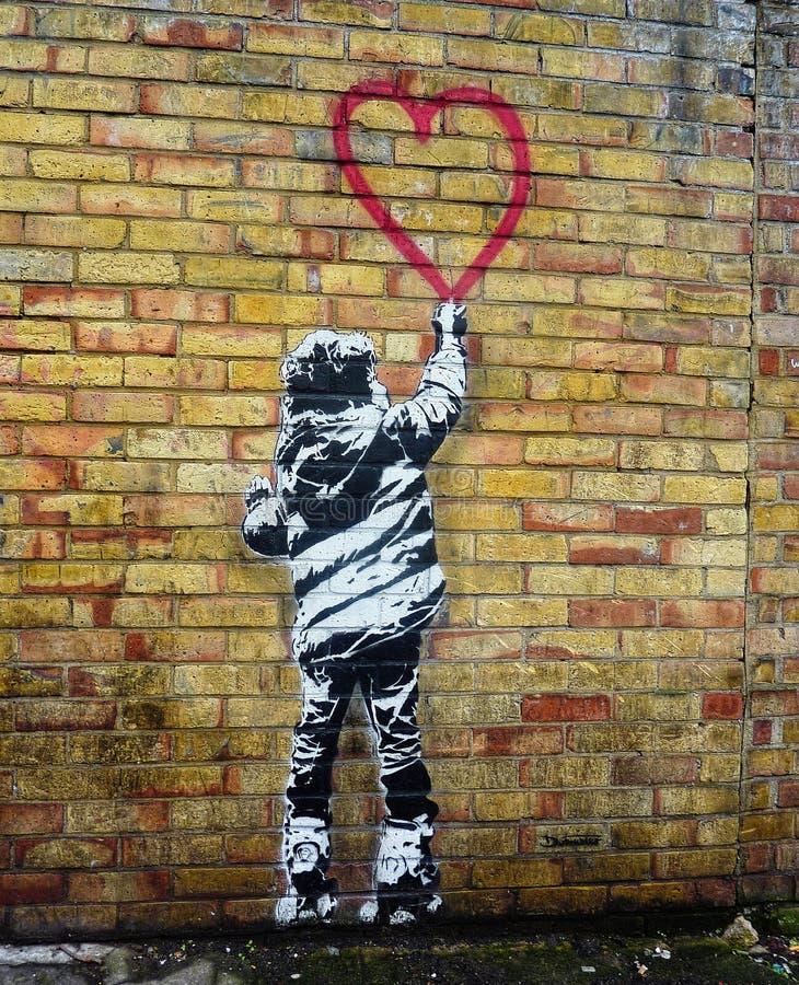 Τέχνη διάτρητων ύφους Banksy Παιδί που χρωματίζει μια μορφή καρδιών στοκ φωτογραφία με δικαίωμα ελεύθερης χρήσης