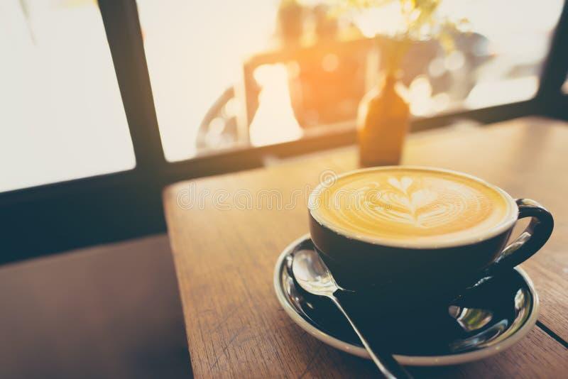 Τέχνη καφέ Latte στο φλυτζάνι στον ξύλινο πίνακα στοκ φωτογραφία με δικαίωμα ελεύθερης χρήσης