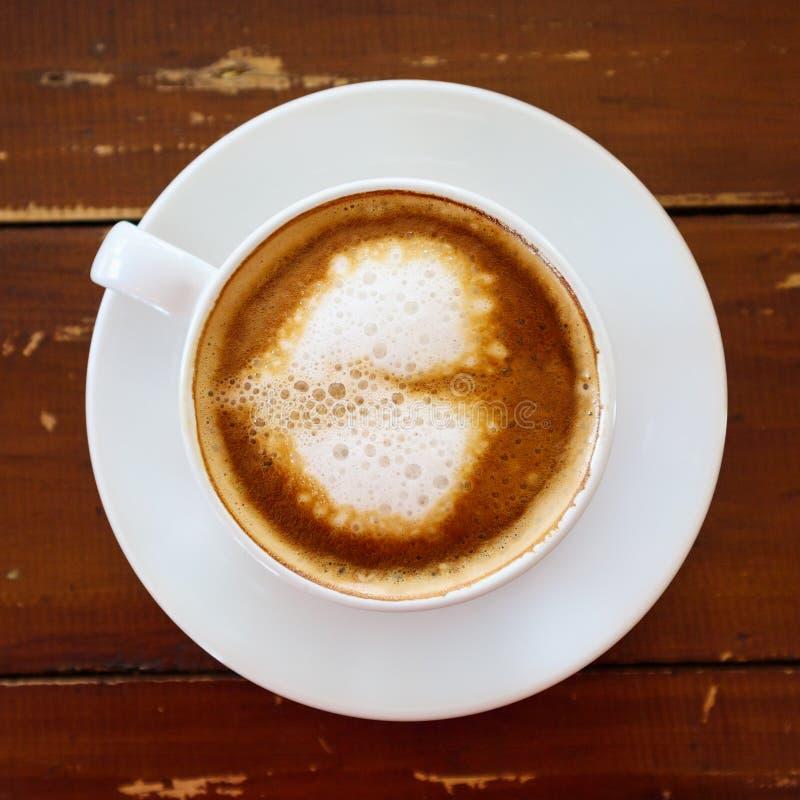 Τέχνη μορφής καρδιών latte στο άσπρο φλυτζάνι καφέ στον ξύλινο πίνακα στοκ φωτογραφία