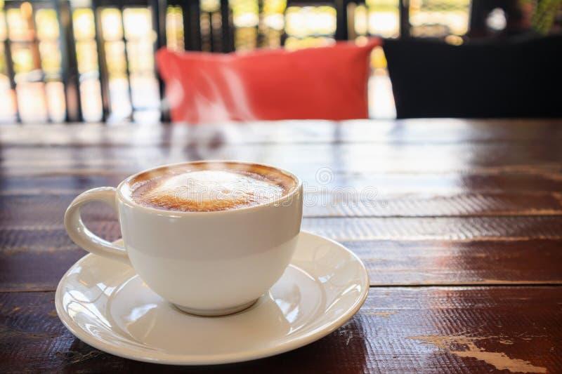 Τέχνη μορφής καρδιών latte στο άσπρο φλυτζάνι καφέ στον ξύλινο πίνακα στοκ εικόνες με δικαίωμα ελεύθερης χρήσης