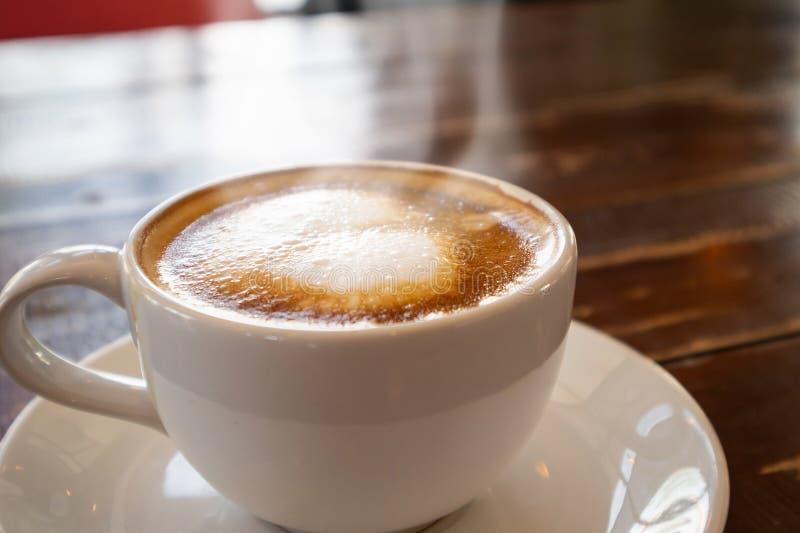 Τέχνη μορφής καρδιών latte στο άσπρο φλυτζάνι καφέ στον ξύλινο πίνακα στοκ φωτογραφία με δικαίωμα ελεύθερης χρήσης