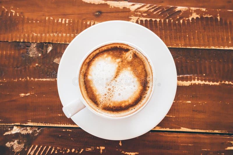 Τέχνη μορφής καρδιών latte στο άσπρο φλυτζάνι καφέ στον ξύλινο πίνακα στοκ εικόνες