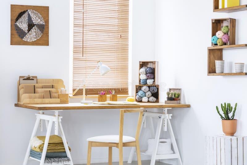 Τέχνη νημάτων DIY σε έναν άσπρο τοίχο ενός Σκανδιναβικού εσωτερικού και δημιουργικού χώρου εργασίας δωματίων τεχνών με το πλέξιμο στοκ φωτογραφία