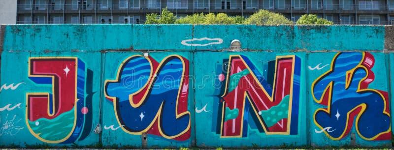 Τέχνη οδών γκράφιτι στον τοίχο στην πόλη που παρουσιάζει παλιοπράγματα λέξης στις κόκκινες και μπλε επιστολές στο μπλε υπόβαθρο στοκ εικόνα