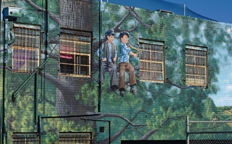 Τέχνη οδών δύο αγοριών που κάθονται στο δέντρο σε Frankston, Αυστραλία στοκ εικόνες