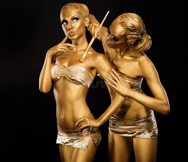 Τέχνη σώματος. Χρωματίζοντας σώμα γυναικών με τη βούρτσα χρωμάτων στο χρυσό χρώμα. Χρυσός αποτελέστε στοκ εικόνες