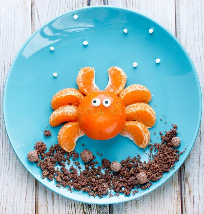 Τέχνη τροφίμων διασκέδασης για τα παιδιά - tangerine αράχνη σε ένα μπλε πιάτο στοκ φωτογραφίες
