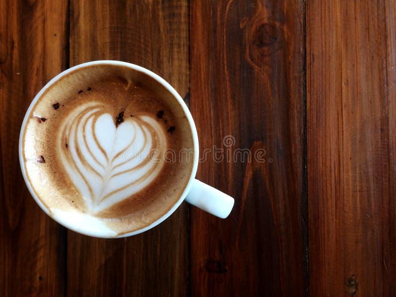 Τέχνη Latte καρδιών αγάπης στο άσπρο κεραμικό φλυτζάνι στον ξύλινο πίνακα στοκ φωτογραφία με δικαίωμα ελεύθερης χρήσης