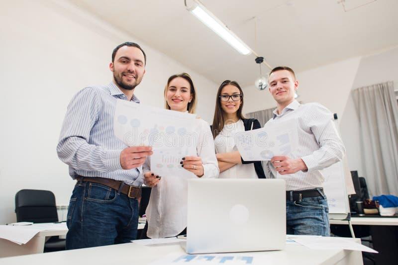 Τέλεια δημιουργική ομάδα Ομάδα τεσσάρων εύθυμων νέων που εξετάζουν τη κάμερα με το χαμόγελο κλίνοντας στον πίνακα μέσα στοκ εικόνες
