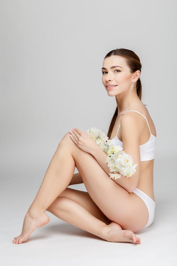 Τέλεια θηλυκά πόδια στο γκρίζο υπόβαθρο στοκ εικόνες