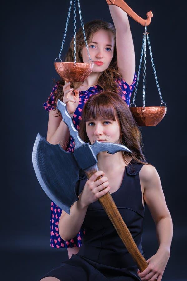 Τίμιο δίκαιο δικαστήριο, που ζυγίζει τα πλεονεκτήματα - και - μειονεκτήματα Τρελλή έννοια αποκριών Κορίτσια με Libra και το τσεκο στοκ εικόνες