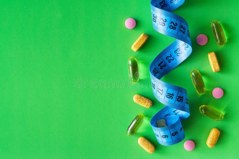 Ταινία και χάπια εκατοστόμετρων σε ένα πράσινο υπόβαθρο με το διάστημα για το κείμενο στοκ εικόνα