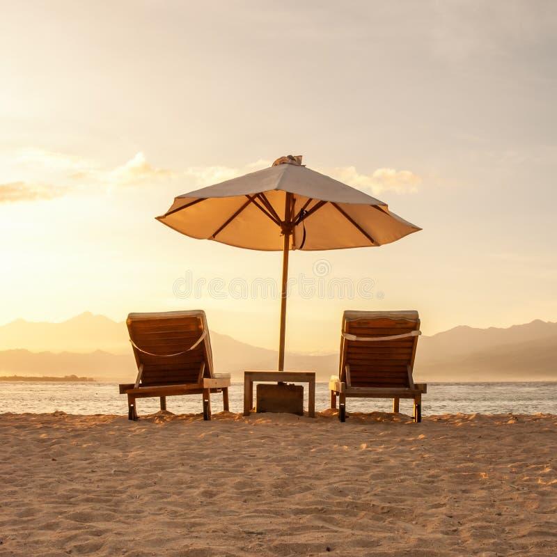Τακτοποιημένη εικόνα δύο όμορφα καρεκλών και parasol ομπρελών σε μια αμμώδη παραλία παραδείσου στοκ εικόνα με δικαίωμα ελεύθερης χρήσης