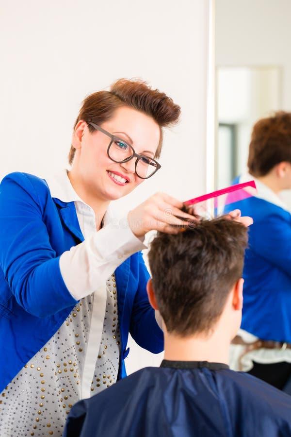 Τακτοποιώντας τρίχα ατόμων κομμωτών στο barbershop στοκ εικόνες